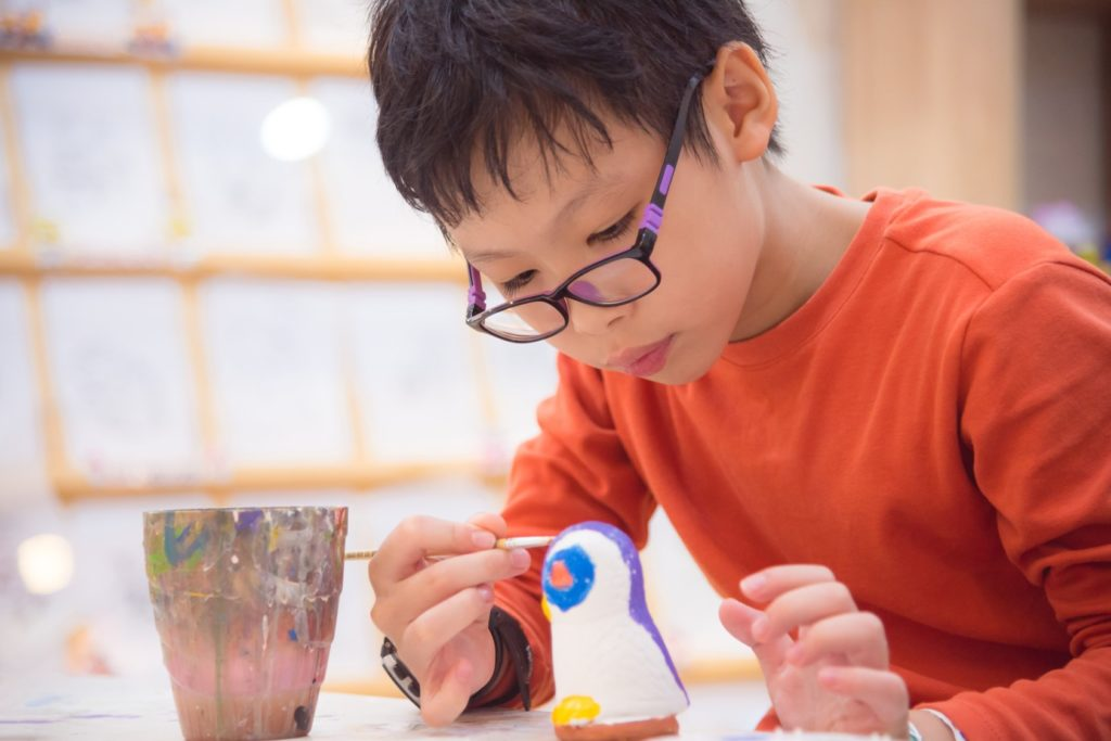 boy painting pottery figure